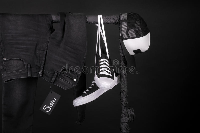 Sale sign. Black and white sneakers, cap pant, jeans hanging on clothes rack background. friday. Copy space. Sale sign. Black and white sneakers, cap and pant royalty free stock photo