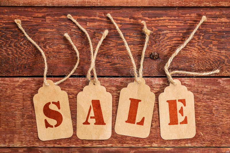 Sale sign on price tags. Sale sign or concept - letters on price tags against rustic red painted barn wood stock images