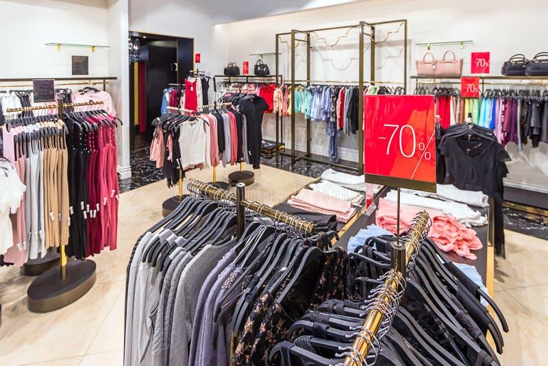 Sale tecken med en rabatt 70% i kvinnornas bekläda lager Färgrika klänningar på hängare i en detaljhandel shoppar Säsongförsäljni royaltyfri foto