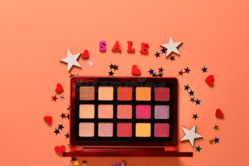 Sale text on an orange background. Professional trendy makeup products with cosmetic beauty products,  eye shadows, eye lashes, royalty free stock photos