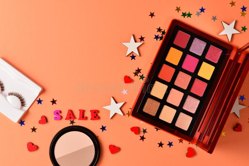 Sale text on an orange background. Professional trendy makeup products with cosmetic beauty products,  eye shadows, eye lashes, stock photos