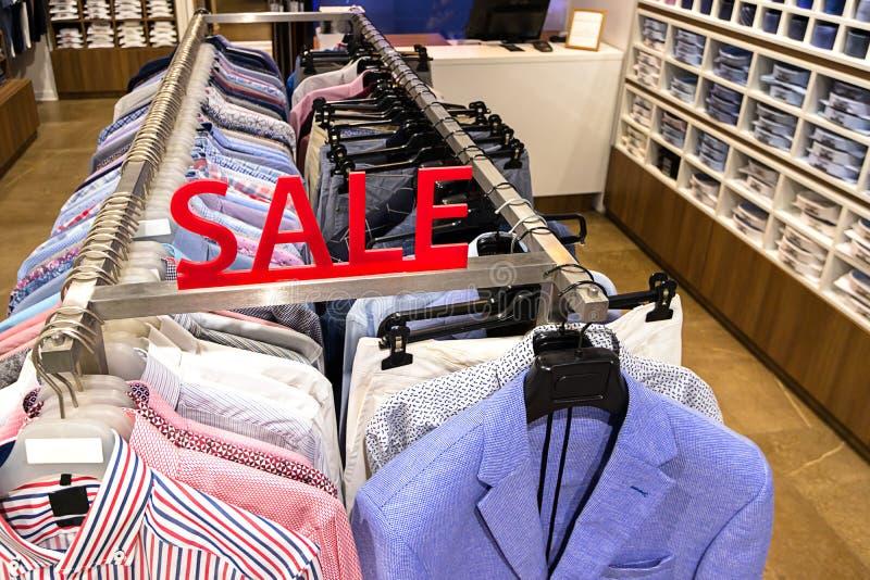 Sale undertecknar in avdelningen av mäns skjortor och omslag i lagret Färgrik kläder på hängare i en detaljhandel shoppar Säsongf arkivfoto