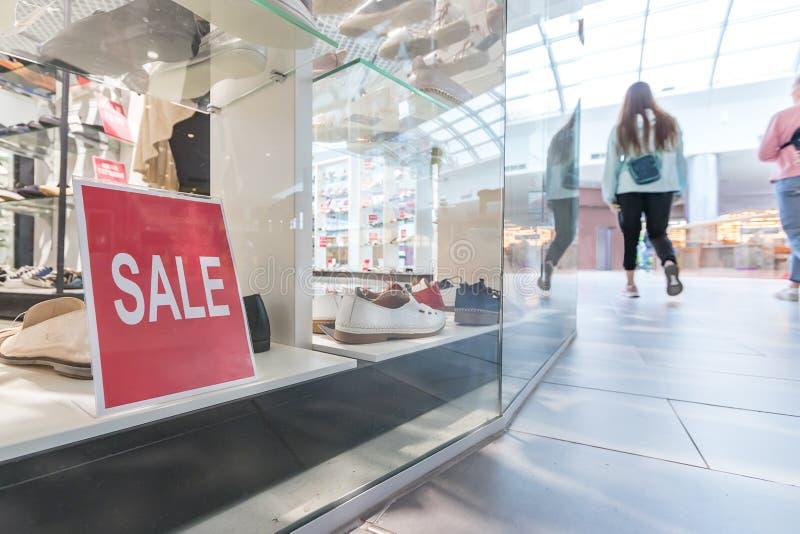 Sale undertecknar i skolagret shoppar fönstret Shoppare går runt om gallerian Säsongförsäljning, mode och shoppingbegrepp royaltyfri foto