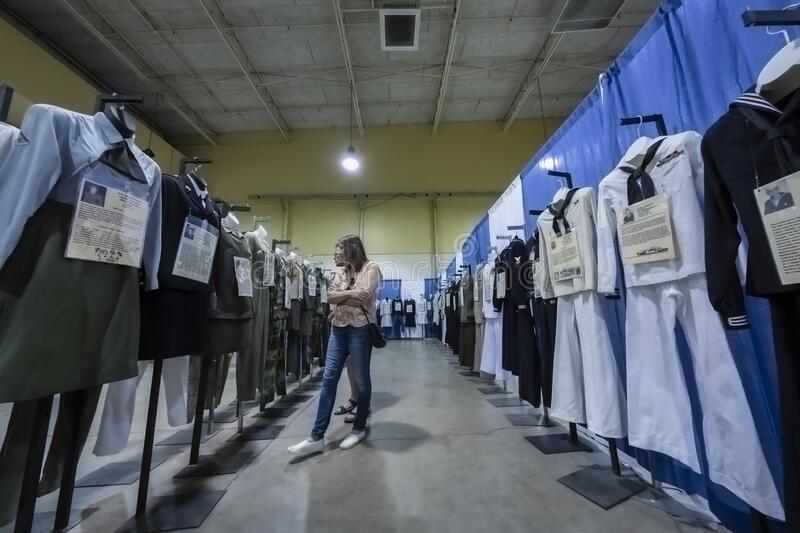 Isolated display of vintage United States military uniforms with a woman viewing the uniforms. Salem, Oregon / USA - July 12, 2019: Isolated display of vintage stock images