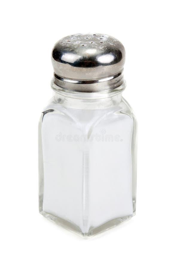 Salero de cristal con la sal aislada imagen de archivo