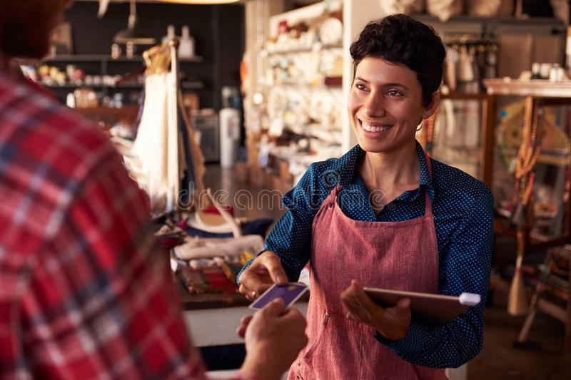 Sales Assistant With Credit Card Reader On Digital Tablet stock images