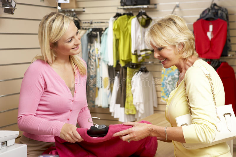 Sales assistant with customer in clothing store. Looking happy stock images