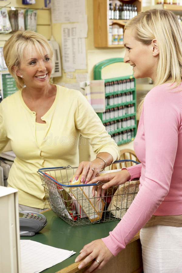 Sales assistant with customer in health food store royalty free stock image