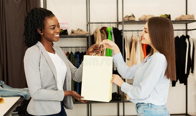 Sales Assistant Giving Package With Clothes To Buyer In Boutique royalty free stock photography