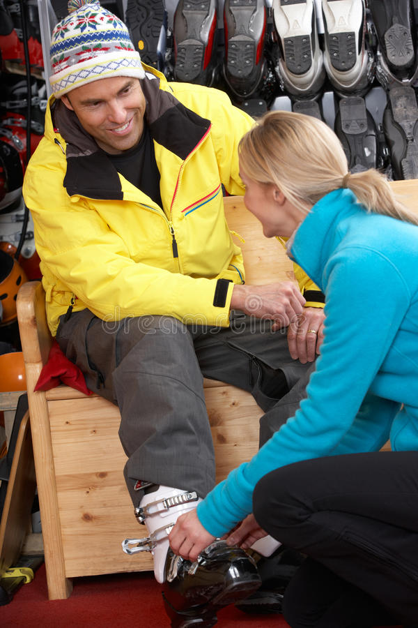 Download Sales Assistant Helping Man To Try On Ski Boots Stock Photo - Image: 25645688