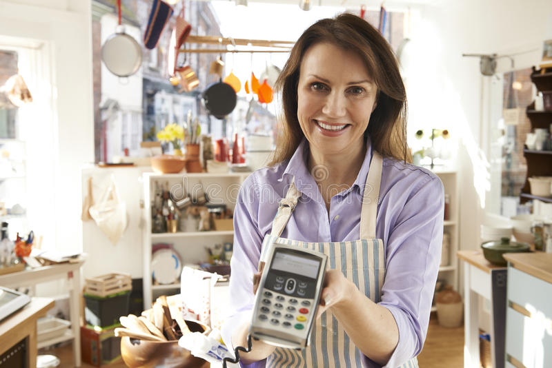 Sales Assistant In Homeware Store With Credit Card Machine royalty free stock image