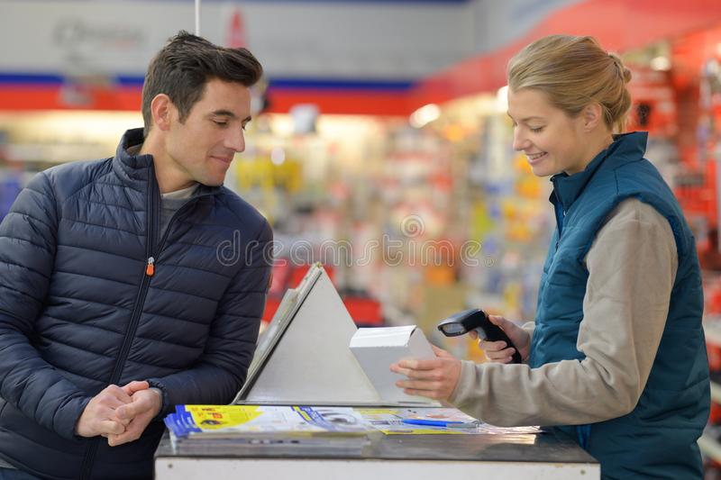 Sales assistant scanning product at checkout. Checkout royalty free stock photos