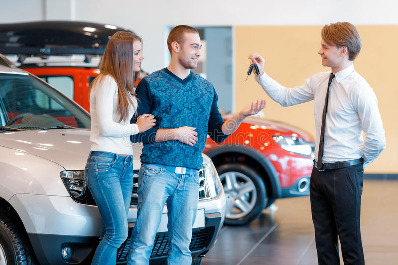 Sales consultant gives keys from new car to young royalty free stock photography