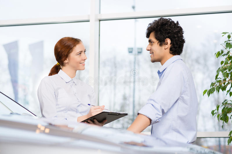 Sales consultant. Young women consultant in show room talking with client royalty free stock photography