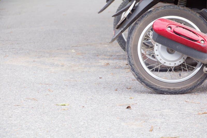 Sales de roue de moto garés en parc public sur la route avec l'espace de copie ajoutent le texte photo libre de droits