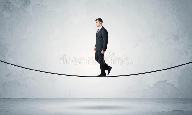 Sales guy balancing on tight rope. A confident businessman with briefcase walking ahead on a tightrope in empty grey urban space concept stock photo