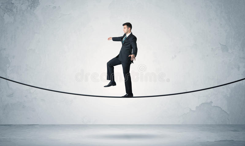 Sales guy balancing on tight rope royalty free stock photo