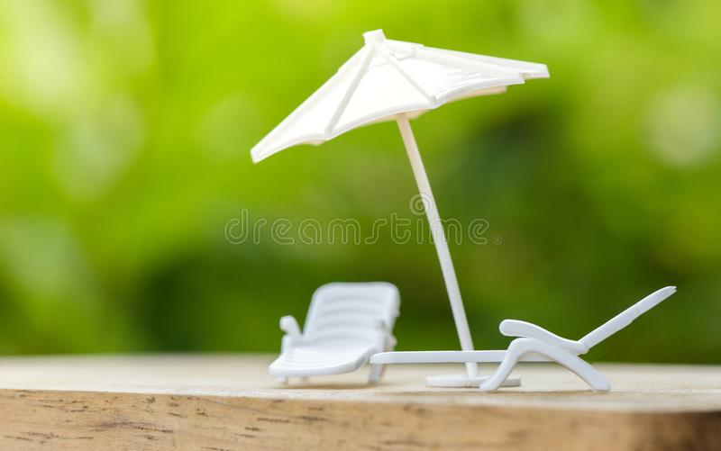 Sales insurance concept or plan relax on holiday umbrella protecting on bench chair for family stock image
