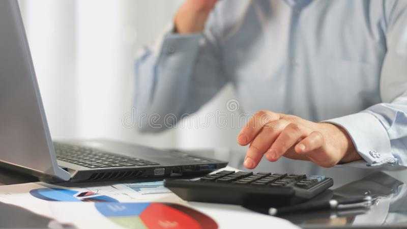 Sales manager calculating company profit, inserting data on laptop, technology. Stock photo royalty free stock photos