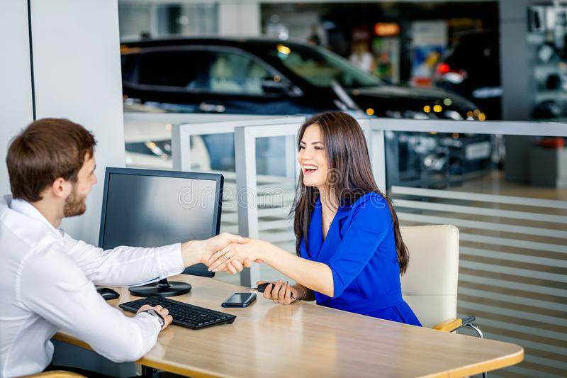 Sales manager and female customer shaking hands congratulating each other at the dealership showroom. royalty free stock image