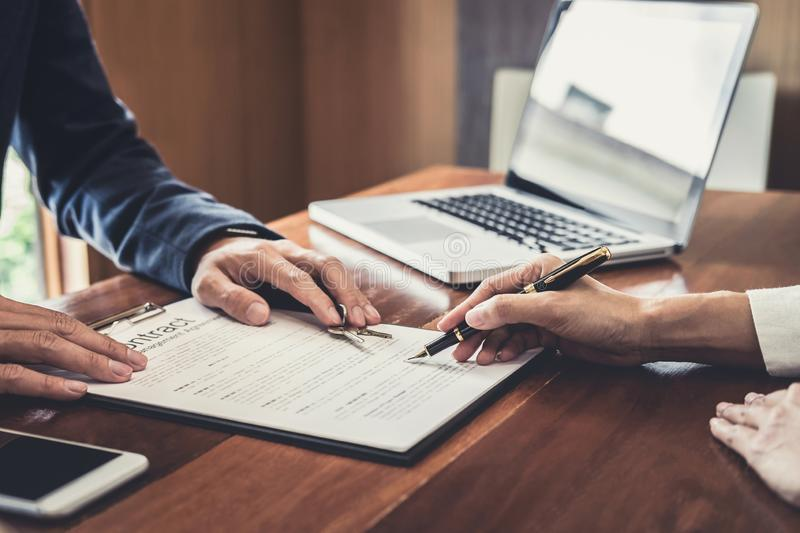 Sales manager filing keys to customer after signing rental lease contract of sale purchase agreement, concerning mortgage loan. Offer for and house insurance royalty free stock image