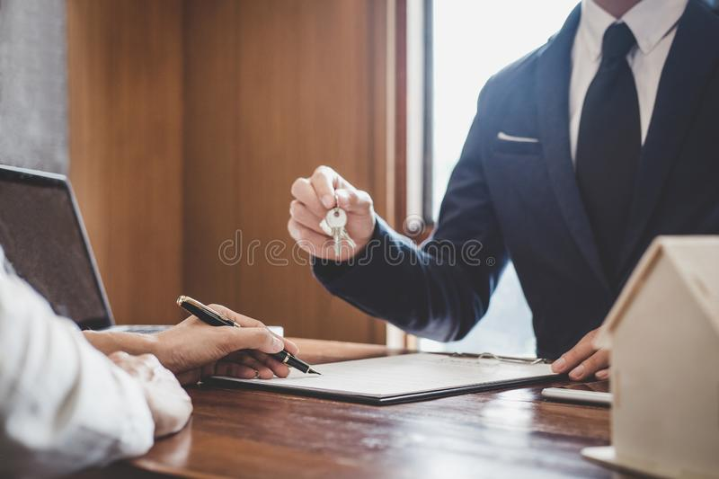 Sales manager filing keys to customer after signing rental lease contract of sale purchase agreement, concerning mortgage loan. Offer for and house insurance royalty free stock photo