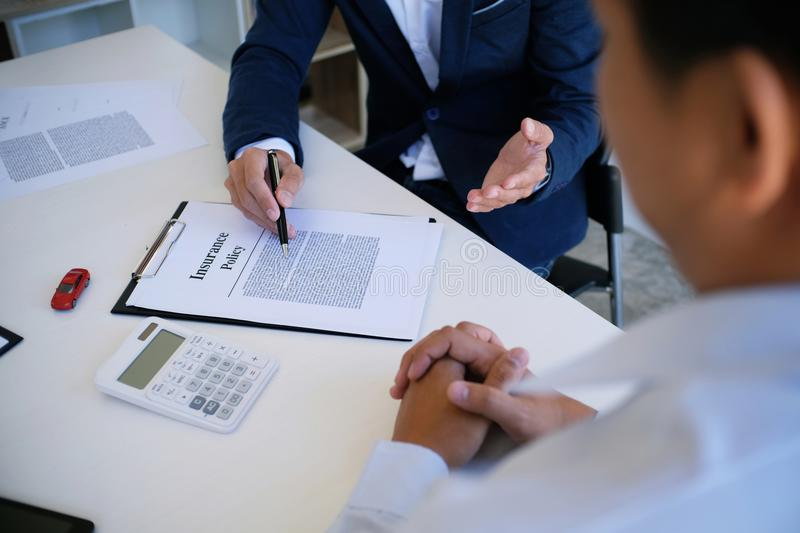 Sales manager giving advice application form document, considering mortgage loan offer for car and house insurance. stock image