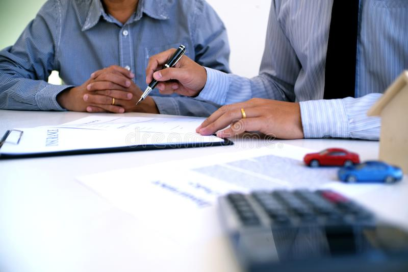 Sales manager giving advice application form document, considering mortgage loan offer for car and house insurance. Sales manager giving advice application form royalty free stock image