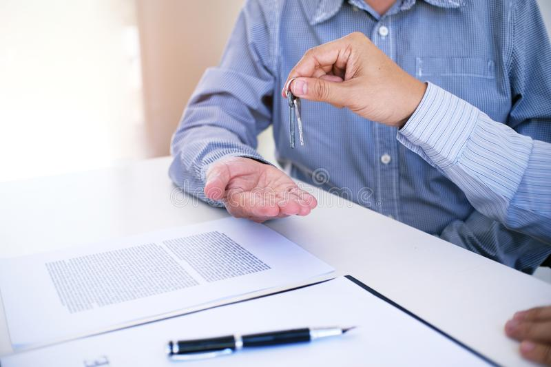 Sales manager giving advice application form document, considering mortgage loan offer for car and house insurance. royalty free stock photo