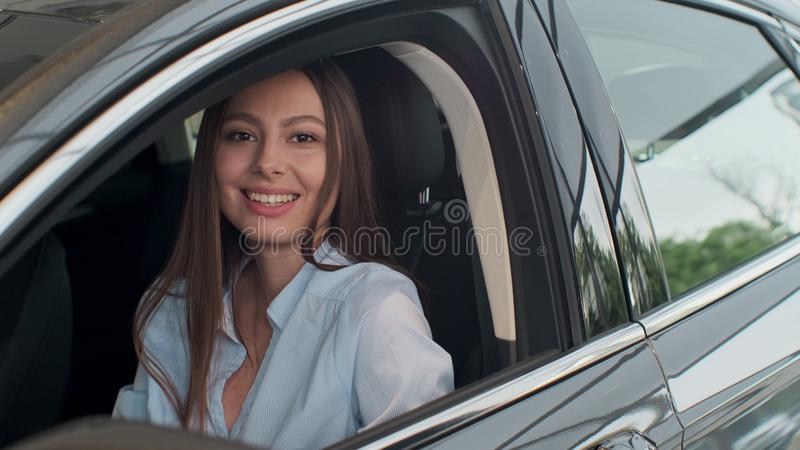 Sales manager handing over the keys to girl that sitting in the car. royalty free stock image