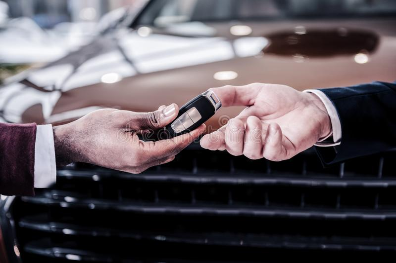 Sales manager passing keys from new brown hatchback car to new owner. Passing keys. Sales manager wearing white shirt and jacket passing keys from new brown royalty free stock photo