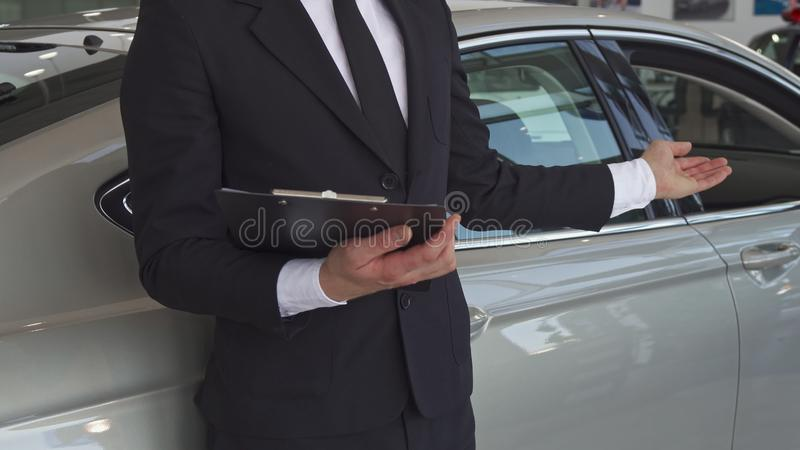 Sales manager points his hand on the car royalty free stock photo