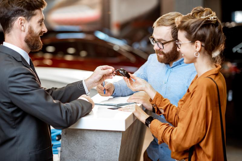 Sales manager with a young couple buying a new car royalty free stock photography