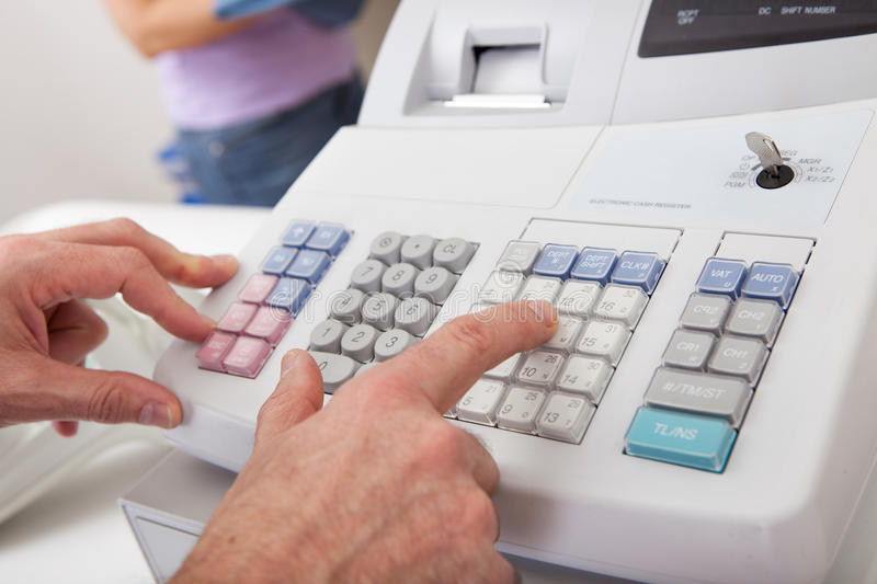 Sales person entering amount on cash register royalty free stock photography