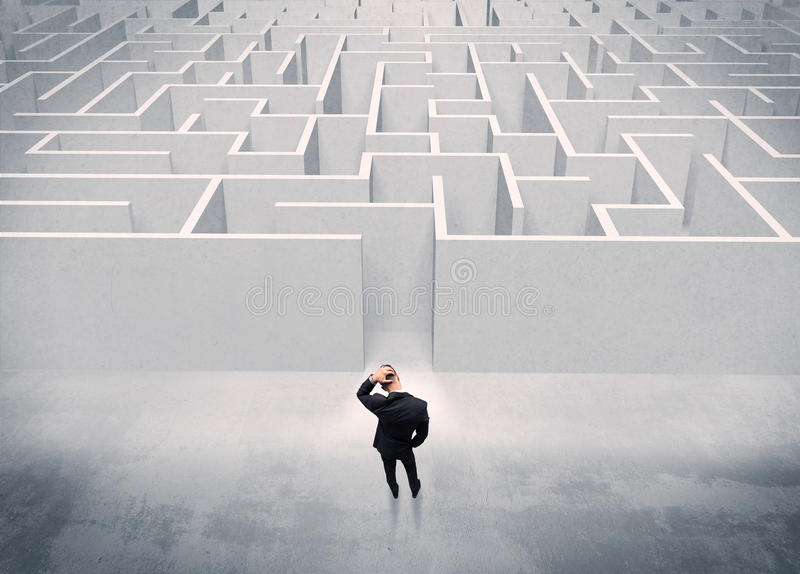 Sales person standing at maze entrance. A good looking businessman with briefcase standing in front of white labirynth entrance about to make a decision concept stock photography