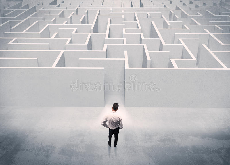 Sales person standing at maze entrance. A good looking businessman with briefcase standing in front of white labirynth entrance about to make a decision concept royalty free stock image