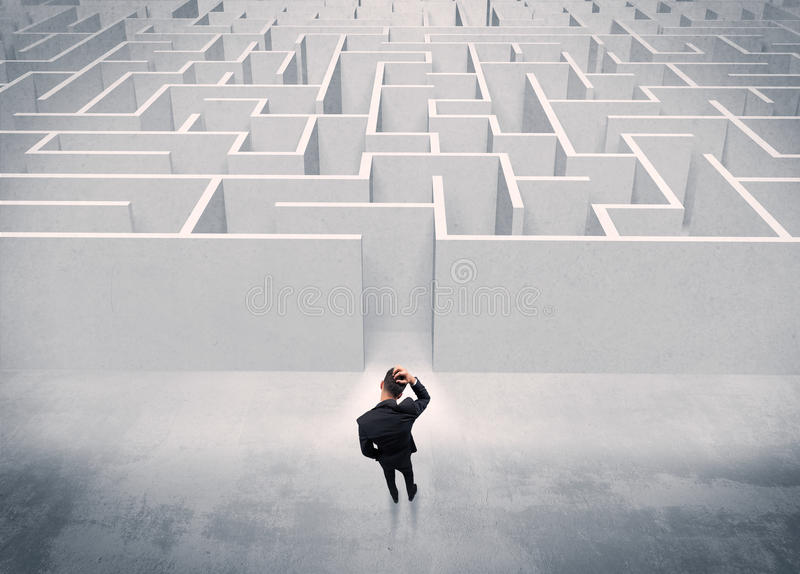 Sales person standing at maze entrance. A good looking businessman with briefcase standing in front of white labirynth entrance about to make a decision concept stock photo