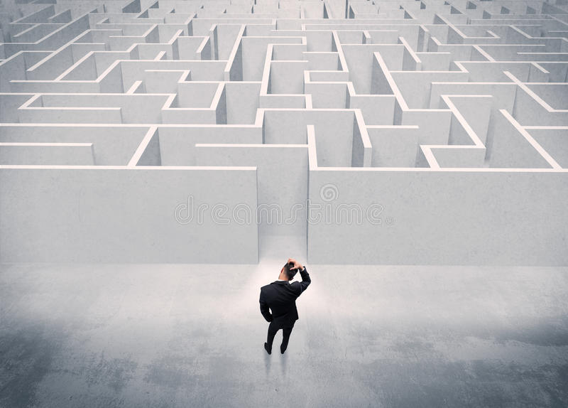 Sales person standing at maze entrance. A good looking businessman with briefcase standing in front of white labirynth entrance about to make a decision concept royalty free stock images