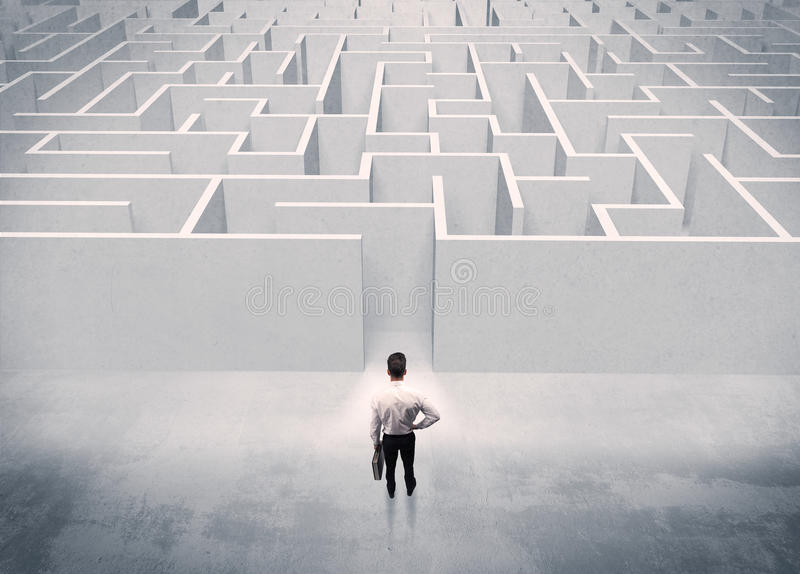 Sales person standing at maze entrance. A good looking businessman with briefcase standing in front of white labirynth entrance about to make a decision concept royalty free stock photo