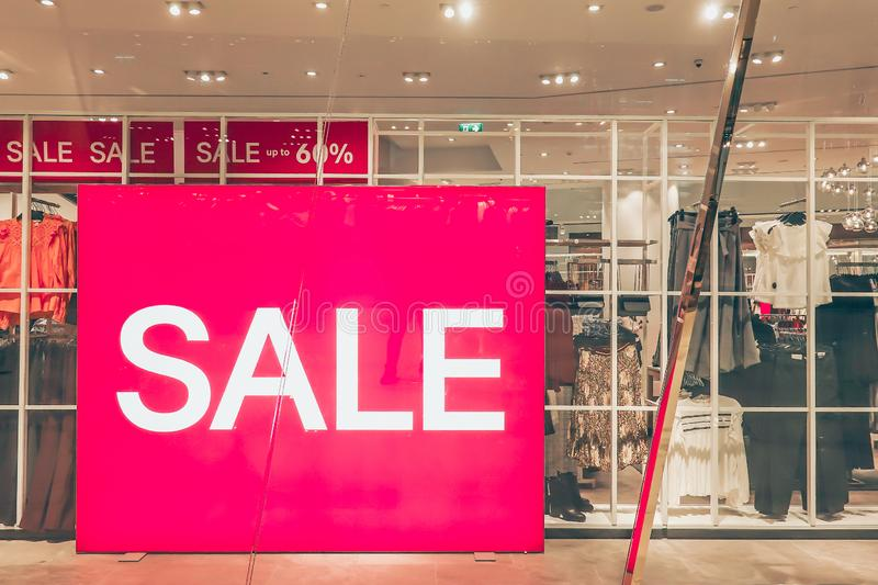 Sales promotion of women fashion clothes retail store in shopping mall, sale label sign sticker in front of shop door glasses. Sales promotion of women fashion royalty free stock photos