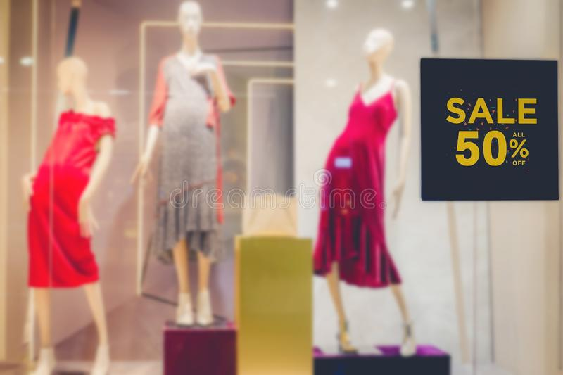 Sales promotion of women fashion clothes retail store in shopping mall, sale label sign sticker in front of shop door glasses. A Sales promotion of women fashion stock photos