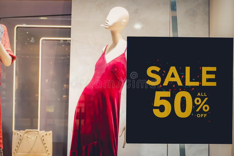 Sales promotion of women fashion clothes retail store in shopping mall, sale label sign sticker in front of shop door glasses. A Sales promotion of women fashion royalty free stock images