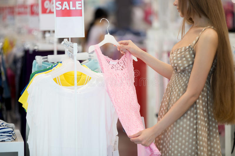 Sales, shopping, fashion concept. Long-haired young pretty woman in shopping centre store choosing clothes looking at pink lace dress standing sideways. Sales royalty free stock image
