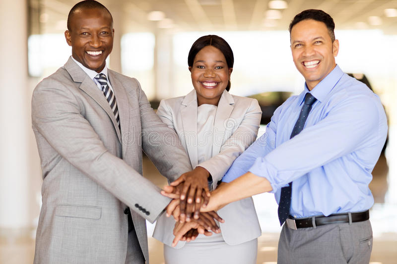 Sales staff hands together. Cheerful sales staff putting hands togerther in vehicle showroom stock image