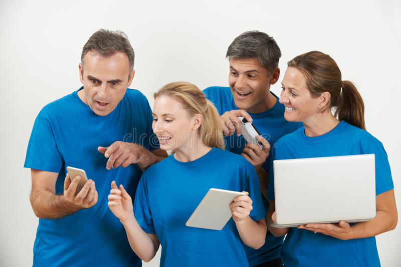 Sales Team Wearing Uniform With Selection Of Techno Gadgets stock image