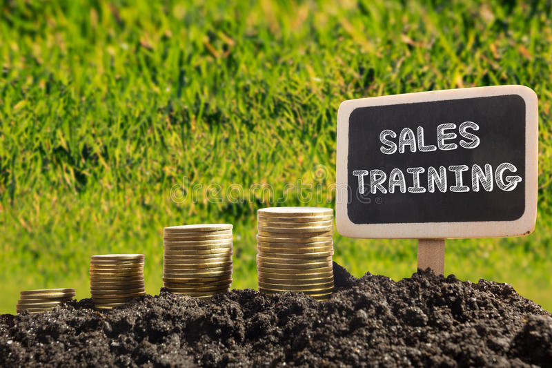Sales training. Financial opportunity concept. Golden coins in soil Chalkboard on blurred urban background. stock photo