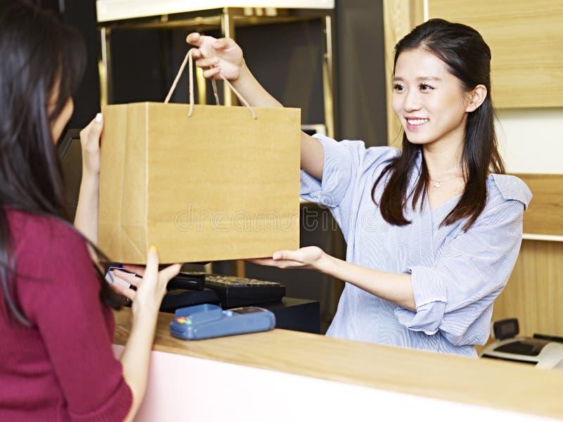 Salesclerk handing merchandise to customer royalty free stock photography