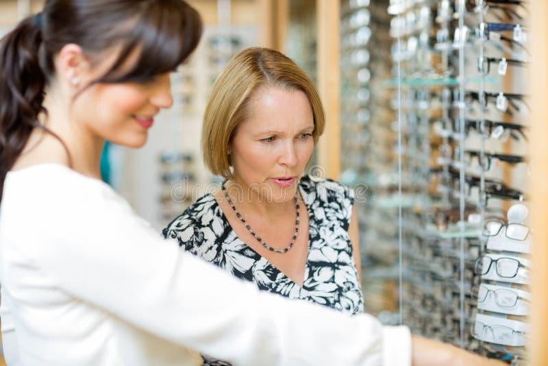 Salesgirl помогая женщине в выбирать стекла стоковые фото