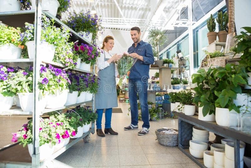 Salesgirl помогая клиенту в покупая цветке стоковая фотография rf
