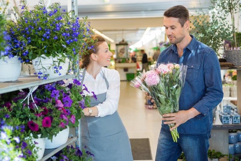 Salesgirl помогая клиенту в покупая цветке стоковое изображение